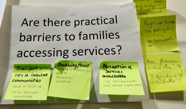 """A sign in a workshop that says """"Are there practical barriers to families accessing services?"""""""